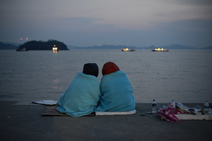 Relatives of victims of the South Korean ferry 'Sewol' sit before the sea at Jindo harbour (AFP Photo / Ed Jones)