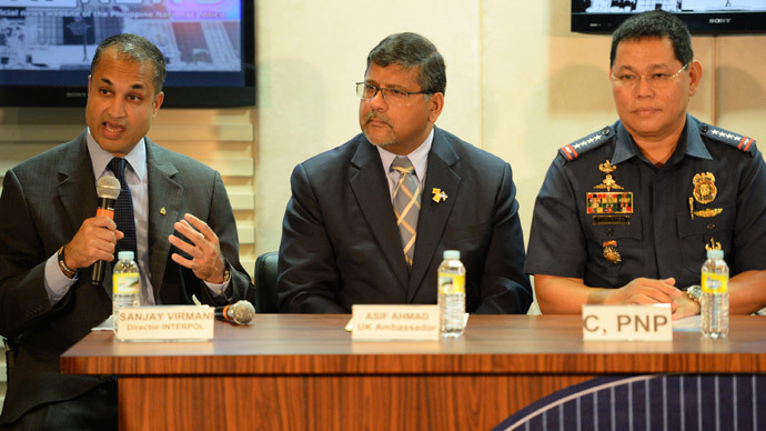 Sanjay Virmani (L), director of Interpol's Digital Crime Centre, gestures as he speaks while Britain's Ambassador to the Philippines Asif ahmad (C) and Philippine police chief Alan Purisima (R) listen during a press conference at the police headquarters in Manila on May 2, 2014. (AFP Photo / Ted Aljibe)