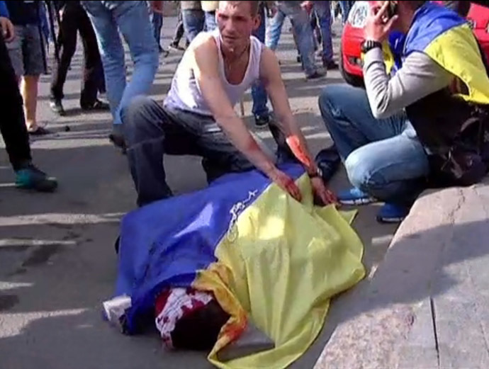 This still grabbed on TV images released by INTER, shows a man covering the bloodied body of a man with an Ukrainian flag during a demonstration on May 2, 2014 in Odessa. (AFP/Inter)