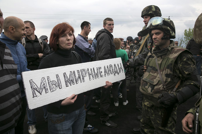 "A civilian holds a sign in front of Ukrainian troops at a checkpoint near the town of Slaviansk in eastern Ukraine May 2, 2014. The sign reads, ""We are peaceful people."" (Reuters/Baz Ratner)"