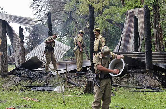 Indian security personnel inspect the debris of the houses that were burnt during attacks at Baksa district in the northeastern Indian state of Assam May 3, 2014. (Reuters)