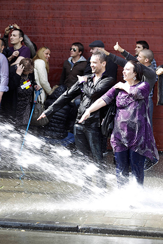 """People make the controversial 'quenelle' gestures as the police uses water cannon to disperse protestors who attempt to participate in an anti-Semitic congress """"European Dissidents' Congress"""" on May 4 2014 in Brussels (AFP Photo / Nicolas Maeterlinck)"""