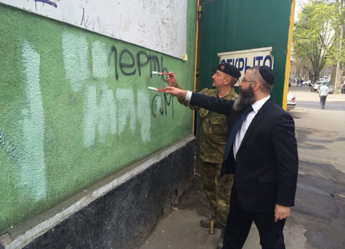 Rabbi Avraham Wolf and UNA-UNSO commander Valery Zagorodny remove anti-Semitic writings. Photo courtesy of the Chabad Odessa Jewish community.