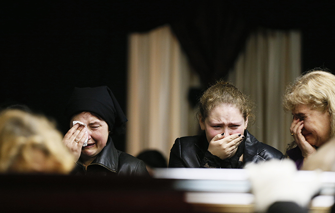 Mourners grieve at the coffin of Vyacheslav Markin, a regional parliament deputy who died in a fire at the trade union building on Friday, at his funeral in Odessa May 5, 2014. (Reuters / Gleb Garanich)