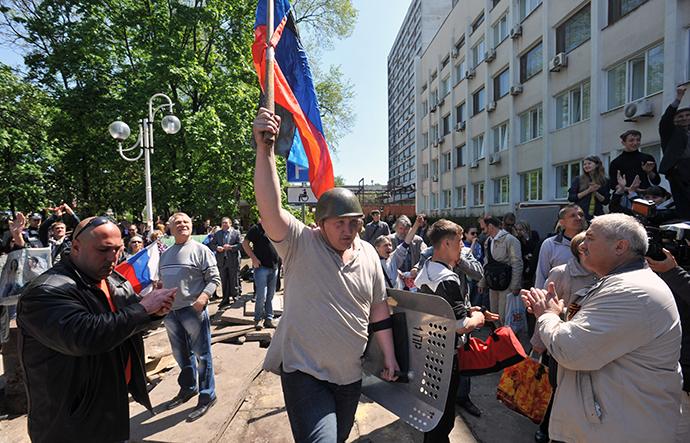 Activists celebrate as Ukrainian policeman leave guarding the state city building in southern Ukrainian city of Mariupol on May 7, 2014. (AFP Photo / Genya Savilov)