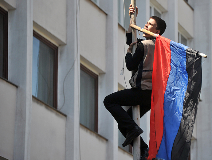 An activist climbs up on the flagpole as he holds flag of so-called Donetsk Republic in the teeth after Ukrainian policemen left their guarding outside of state city building in southern Ukrainian city of Mariupol on May 7, 2014. (AFP Photo / Genya Savilov)