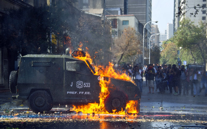 A riot police armored car is hit by a molotov cocktail thrown by students during a protest against the education system on May 8, 2014 in Santiago. (AFP Photo)