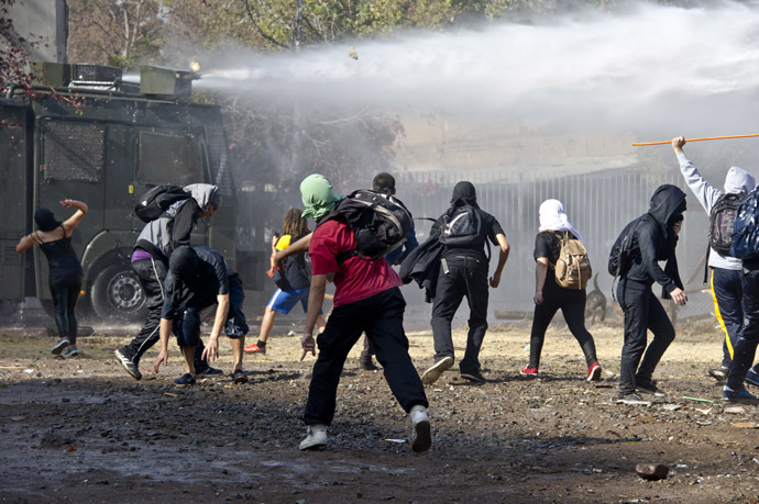 Students clash with riot police during a protest against the education system, in Santiago, on May 8, 2014.(AFP Photo)