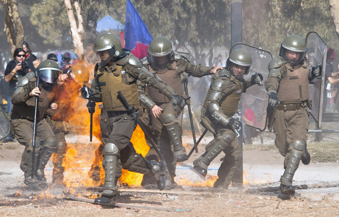 Riot policemen scatter as a molotov cocktail thrown by students falls amid them during a protest against the education system on May 8, 2014 in Santiago. (AFP Photo)