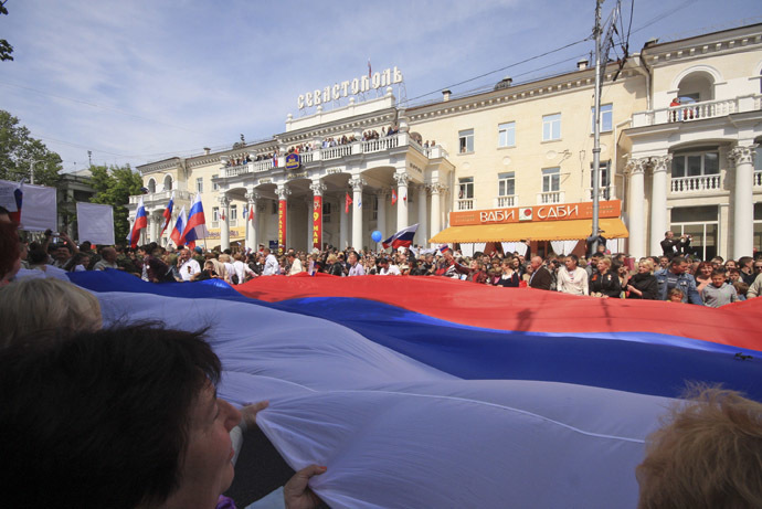 People hold a giant Russian flag during celebrations to mark Victory Day in the Crimean port of Sevastopol May 9, 2014. (Reuters)