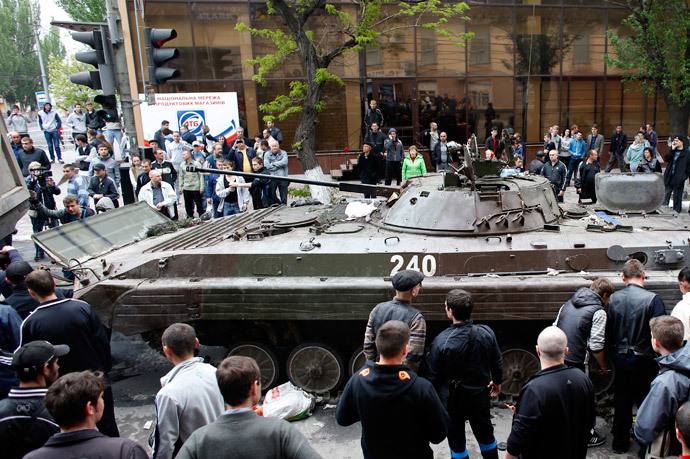 A broken armoured vehicle left behind by Ukrainian forces is taken away by pro-Russian militants in Mariupol May 9, 2014.(Reuters / Marko Djurica)