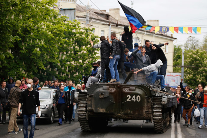 People climb an armored vehicle captured after Ukrainian forces attacked police headquarters in Mariupol. May 9, 2014.(Reuters / Marko Djurica)