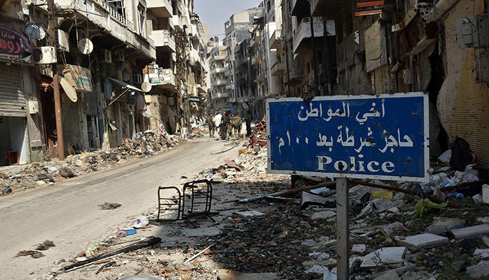 A road sign is seen as Syrian government forces walk in a street on May 9, 2014 in the Christian neighborhood of Hamidiyeh in the old city of Homs after Syrian government forces regained control of rebel-controlled areas. (AFP Photo / Youssef Karwashan)
