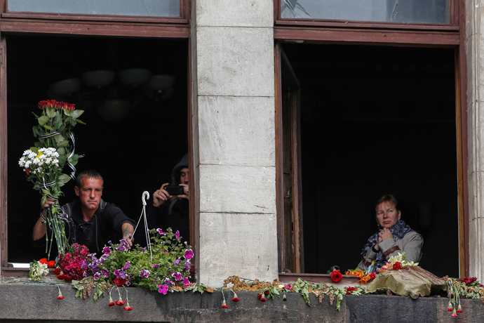 Local residents lay flowers at broken windows of a burnt trade union building before an Orthodox ceremony to mourn the deaths of pro-Russian supporters killed last week during street battles between pro-Russian and pro-Ukrainian supporters, in the Black Sea port of Odessa May 10, 2014 (Reuters / Yevgeny Volokin)