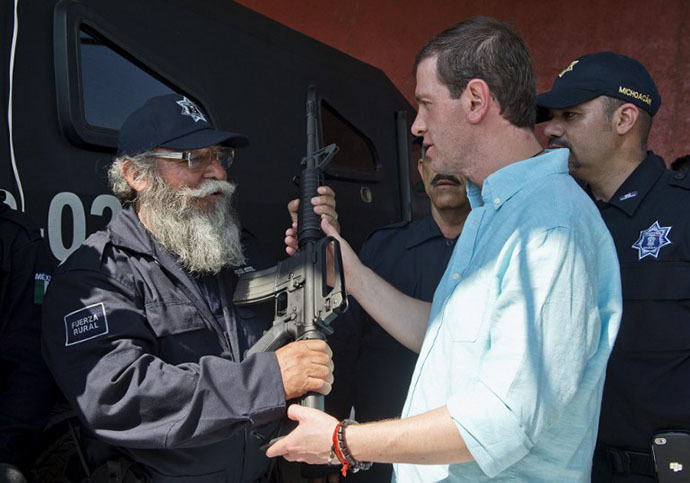 "Estanislao Beltran (L), aka ""Papa Pitufo"" (Papa Smurf in English), leader of the local self-protection police, wearing his new uniform of the rural police, receives an AR-15 assault rifle from the Commissioner for Development and Security of Michoacan, Alfredo Castillo, in Tepalcatepec, Michoacan State, Mexico, on May 10, 2014.(AFP Photo / Ronaldo Schemidt)"