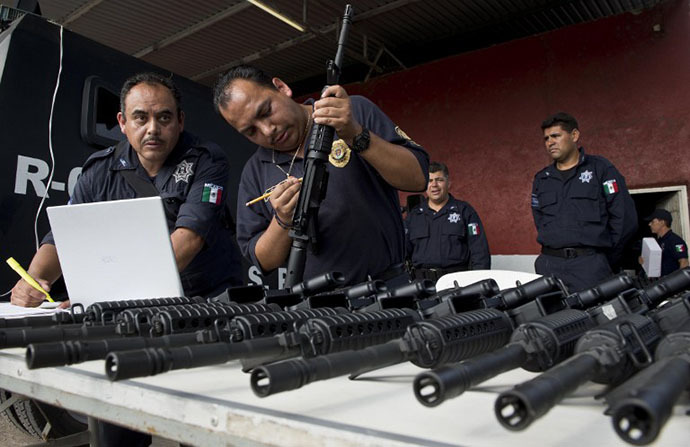 Police officers of the Michoacan state write down the registration numbers of the weapons to be delivered to the newly created rural police, in Tepalcatepec, Michoacan State, Mexico, on May 10, 2014. (AFP Photo / Ronaldo Schemidt)