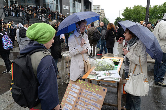 A woman (C) sells bags and caps on which are drawn cannabis leafs while people take part in a protest to call for the legalization of marijuana on May 10, 2014 in Paris. (AFP Photo / Pierre Andrieu)