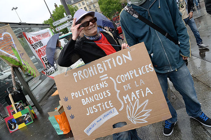 "A woman holds a placard reading ""Prohibition equals politicians, banks, justice, all accomplices of the Mafia"" as she takes part in a protest to call for the legalization of marijuana on May 10, 2014 in Paris. (AFP Photo / Pierre Andrieu)"
