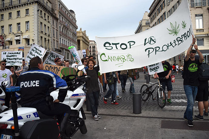 "People hold a banner reading ""Stop the prohibition"" as they face policemen during a protest to call for the legalization of marijuana on May 10, 2014, at the Old Harbour in Marseille, southern France. (AFP Photo / Anne-Christine Poujoulat)"