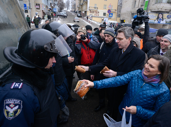 U.S. Assistant Secretary of State for European and Eurasian Affairs Victoria Nuland (R) and U.S. Ambassador Geoffrey Pyatt (2nd R) distribute bread to riot police near Independence square in Kiev December 11, 2013 (Reuters)