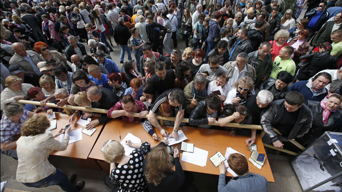 People stand in a line to receive ballots from members (front) of a local election commission during the referendum on the status of Donetsk region in the eastern Ukrainian city of Mariupol May 11, 2014. (Reuters/Marko Djurica)