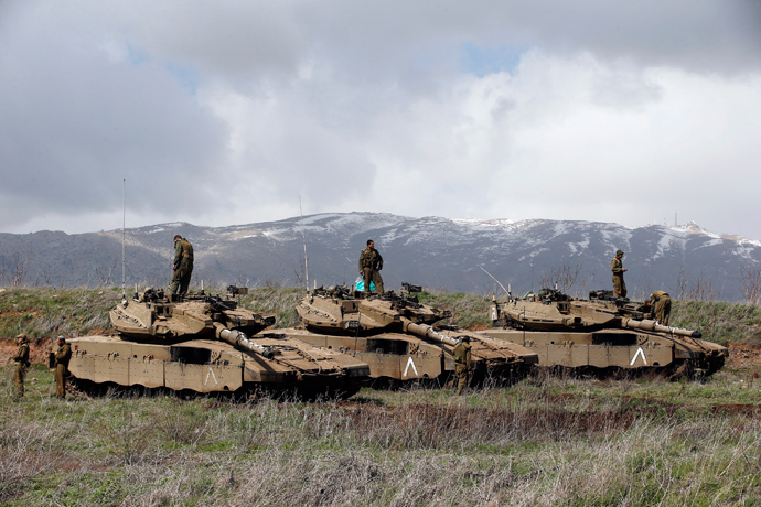 Israeli soldiers stand atop tanks in the Golan Heights near Israel's border with Syria March 19, 2014 (Reuters / Ronen Zvulun)