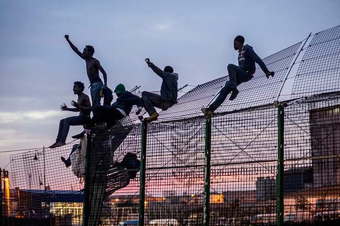 Would-be immigrants react on a fence into the north African Spanish enclave of Melilla on March 28, 2014 after an attempt of dawn assault to cross into the Spanish city, which lies on the northern tip of Morocco (AFP Photo / Jose Colon)