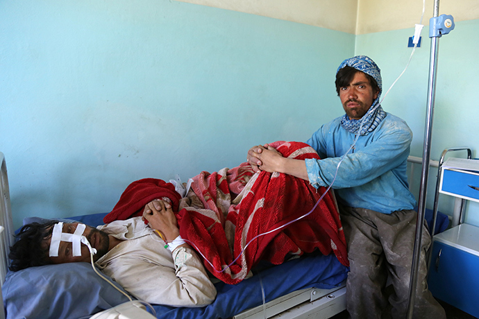 A wounded Afghan patient (L) rests in a hospital bed as a companion looks on following an attack in Ghazni province on May 12, 2014 (AFP Photo)