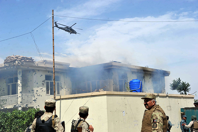 A NATO helicopter hovers as smoke rises from the site of a suicide attack in Jalalabad province on May 12, 2014 (AFP Photo / Noorullah Shirzada)