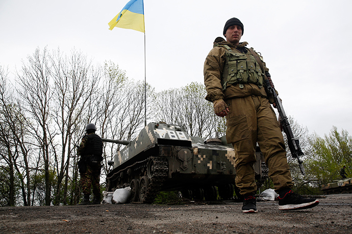 Ukrainian soldiers stand guard in front of armoured personnel carriers at a check point near the village of Malinivka, southeast of Slavyansk, in eastern Ukraine April 29, 2014 (Reuters)