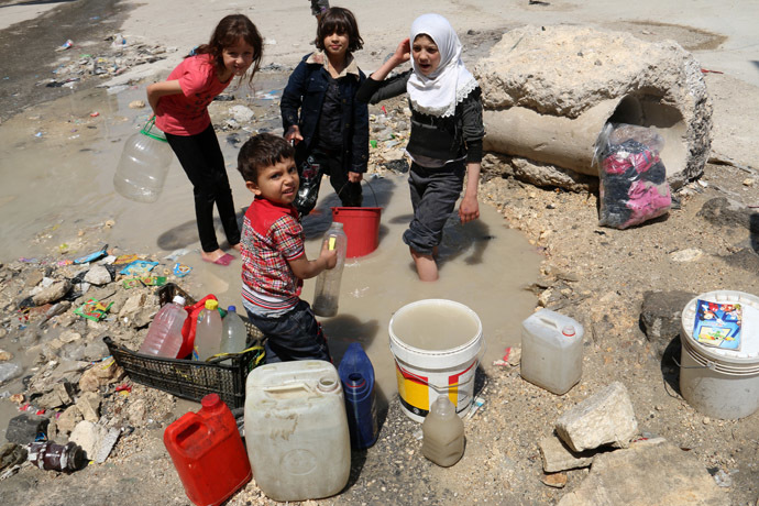 Syrian children collect buckets of stagnant murky water from the side of a road in a rebel-held area in the northern city of Aleppo on May 12, 2014. (AFP Photo/Zein Al-Rifai)