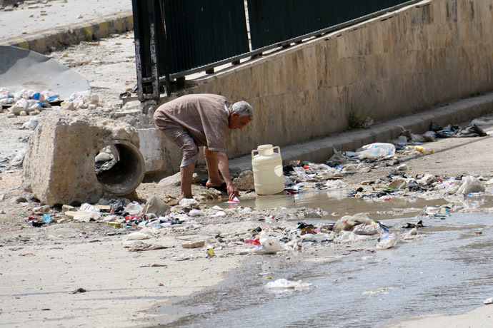 A man collects stagnant murky water from the side of a road in a rebel-held area in Aleppo on May 12, 2014. (AFP Photo/Zein Al-Rifai)