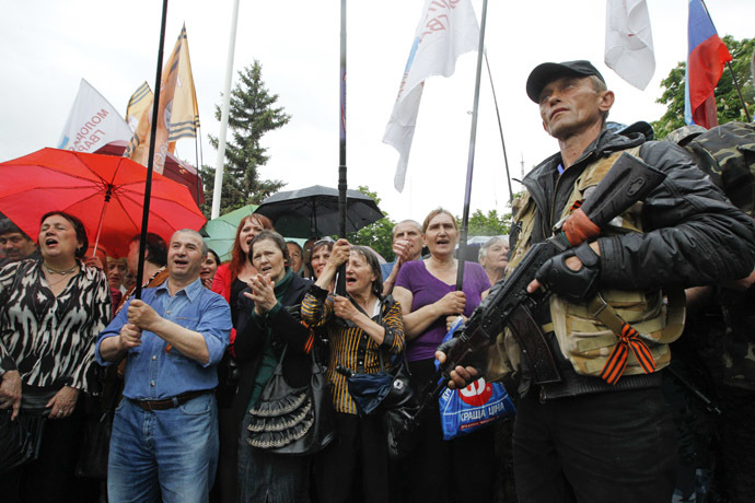 An anti-Kiev armed man stands guard as people hold a rally to mark and celebrate the announcement of the results of the referendum on the status of Luhansk region in Luhansk May 12, 2014. (Reuters/Valentyn Ogirenko)