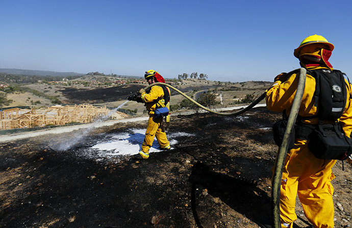 Fire-fighters work to put out spot fires caused by strong winds as they keep close watch over the Bernardo fire north of San Diego, California May 14, 2014. (Reuters / Sandy Huffaker)