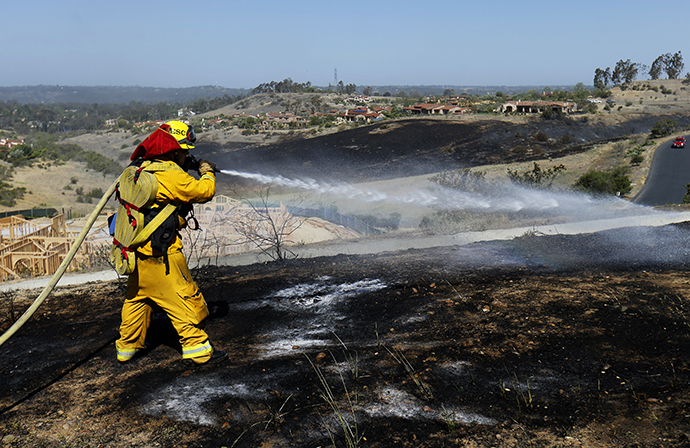 A fire-fighter works to put out spot fires caused by strong winds as they keep close watch over the Bernardo fire north of San Diego, California May 14, 2014. (Reuters / Mike Blake)