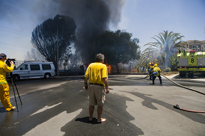 Greg Saska watches his mother's house burn as firefighters battle a fire in Carlsbad, California May 14, 2014. (Reuters / Sam Hodgson)
