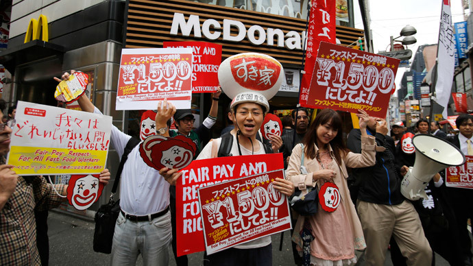 Demonstrators holding posters march during a protest to demand higher wages for fast-food workers in front of a McDonald's fast-food restaurant in Tokyo's Shibuya shopping and amusement district May 15, 2014.(Reuters / Toru Hanai )