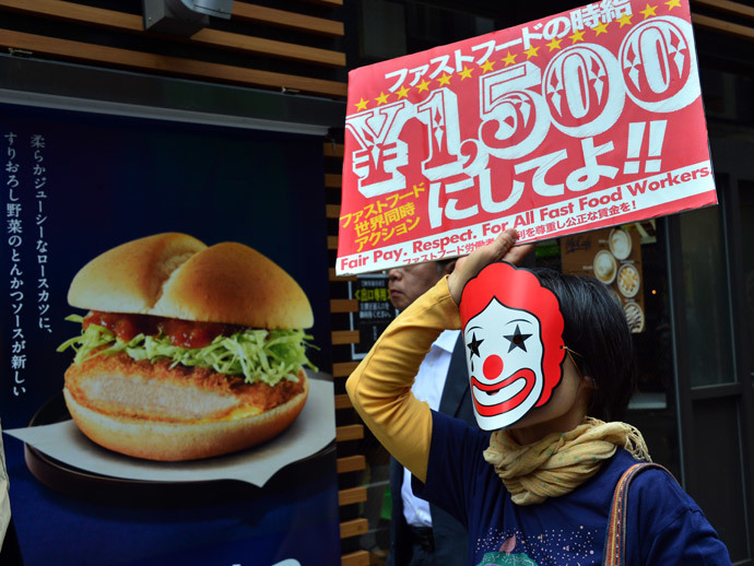 A labour union member holds a placard to demand payment of 1,500 yen (15 USD) an hour for a part-time job at a McDonald's fast-food restaurant in Tokyo on May 15, 2014.(AFP Photo / Yoshikazu Tsuno)