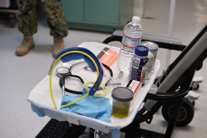 """This photo reviewed by the US military and made during an escorted visit shows a US naval medic explaining the """"feeding chair"""" procedures at the detention facility in Guantanamo Bay, Cuba.(AFP Photo / Mladen Antonov)"""
