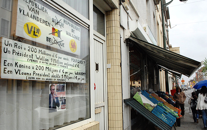 Pedestrians walk on the pavement, 14 May 2007, a few meters next of two billboards pasted on a shopwindow by a local resident of Ninovse Steenweg, Sint-Jans-Molenbeek / Chaussee de Ninove, Molenbeek-Saint-Jean, expressing his opinion in favour of two republics ie Flanders and Wallonia, instead of the Belgium monarchy (AFP Photo / Herwig Vergult)
