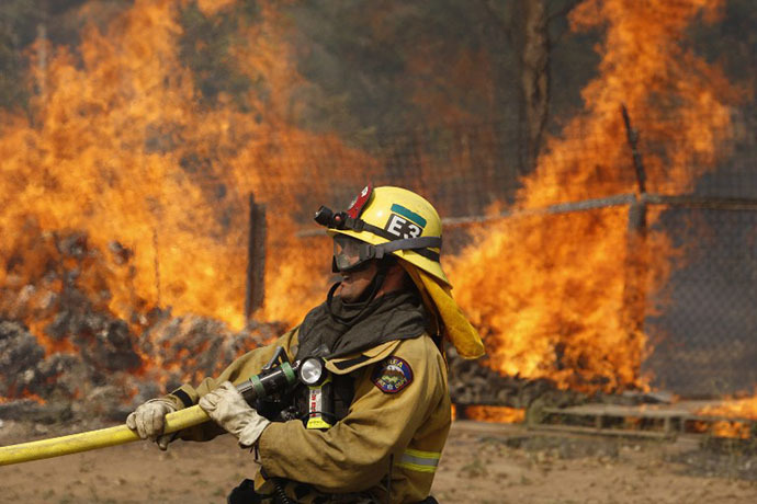 A firefighter pulls a hose in position while battling the Cocos fire on May 15, 2014 in San Marcos, California. (AFP Photo / David Mcnew)