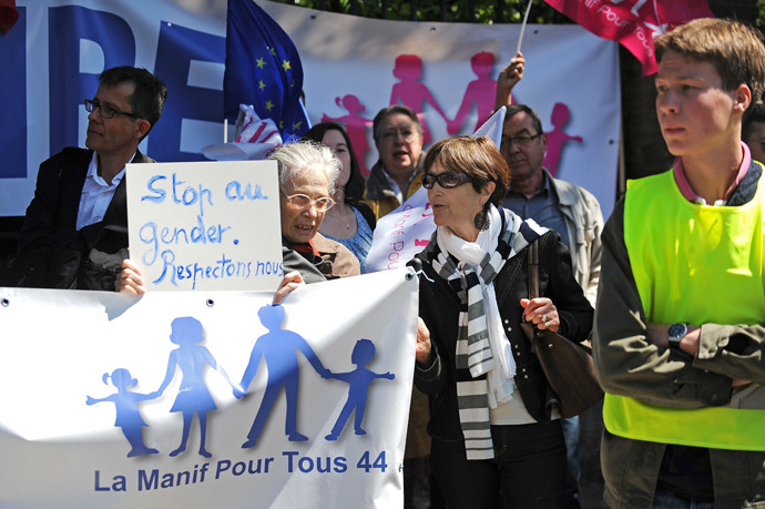 An anti-gay marriage protester of 'La Manif pour tous' movement holds a sign reading 'stop the gender, let's respect ourselves' as she protests with other people against the so called 'Ce que souleve la jupe' ('What raises the skirt') event in high schools on May 15, 2014, in front of the Clemenceau high school in Nantes, western France.(AFP Photo / Jean-Sebastien Evrard )