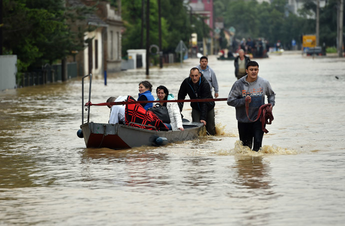 People walk through a flooded street in Obrenovac, 40 kilometers west of Belgrade, on May 16, 2014. (AFP Photo/Andrej Isakovic)