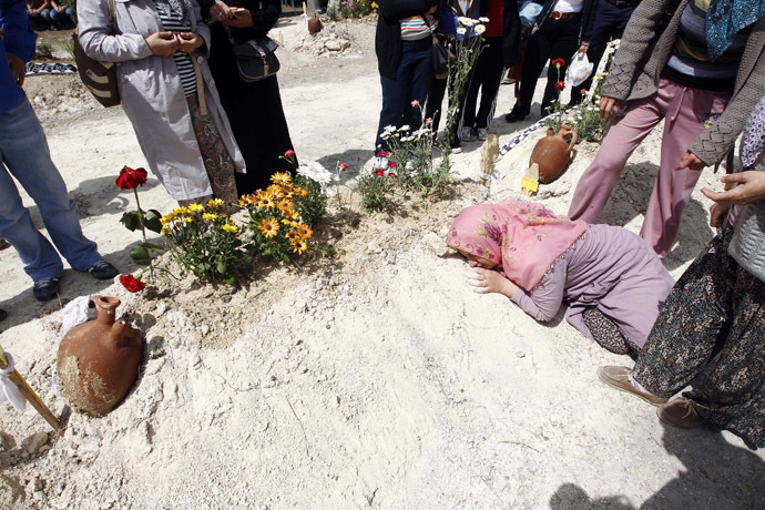Relatives of a miner mourn beside his grave after a mining disaster in Soma, a district in Turkey's western province of Manisa May 16, 2014. (Reuters/Osman Orsal)