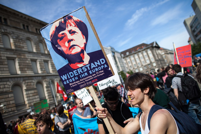 A protester holds a banner featuring German chancellor Angela Merkel reading 'resistance against her Europe' during a Blockupy movement protest on May 17, 2014 in Berlin. (AFP Photo/DPA/Maja Hitji)