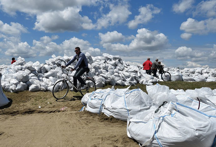 A man rides a bicycle among sand bags protecting the banks of the Sava river in the Serbian city of Sremska Mitrovica, 70 kilometers west of Belgrade, on May 18, 2014. (AFP Photo / Andrej Isakovic)