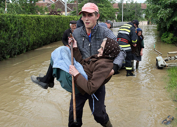 A Serbian rescuer carries an elderly woman out of her flooded house in the village of Obrez, near the central Serbian town of Varvarin, south of Belgrade, on May 17, 2014. (AFP Photo / Sasa Djordjevic)