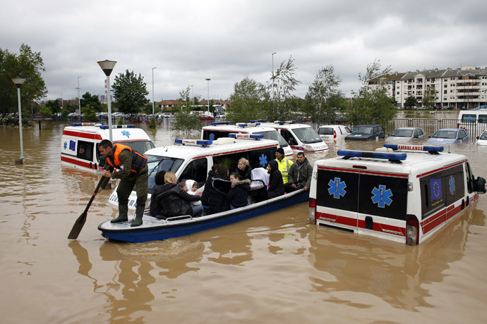 A Serbian rows a boat past flooded ambulance vehicles in the flooded town of Obrenovac, southwest of Belgrade, Serbia May 17, 2014. (Reuters/Marko Djurica)
