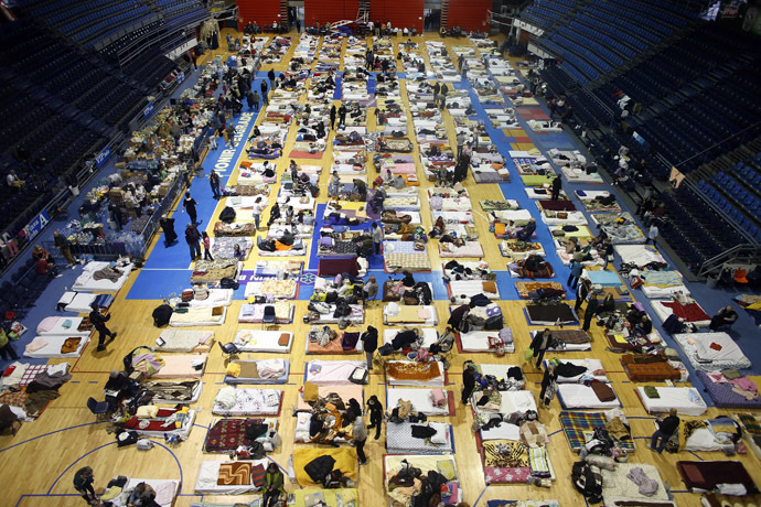 Evacuees from the Serbian town of Obrenovac are seen lying on beds in a shelter hall in Belgrade, May 18, 2014. (Reuters/Marko Djurica)