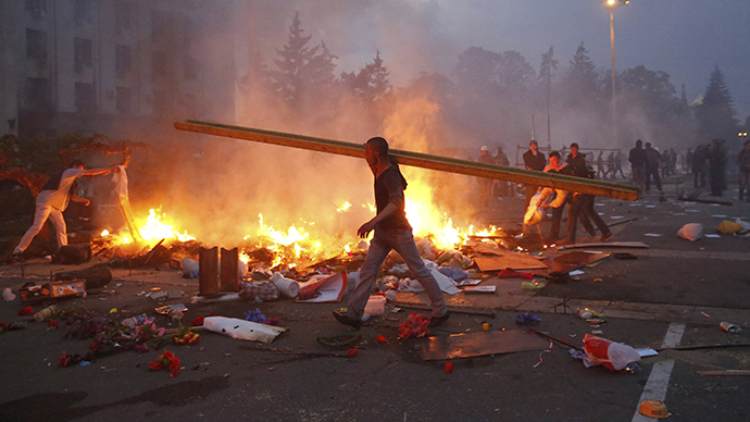 A pro-Kiev protester walks past a burning anti-Kiev tent camp near the Trade Union Building in Odessa May 2, 2014. (Reuters / Yevgeny Volokin)